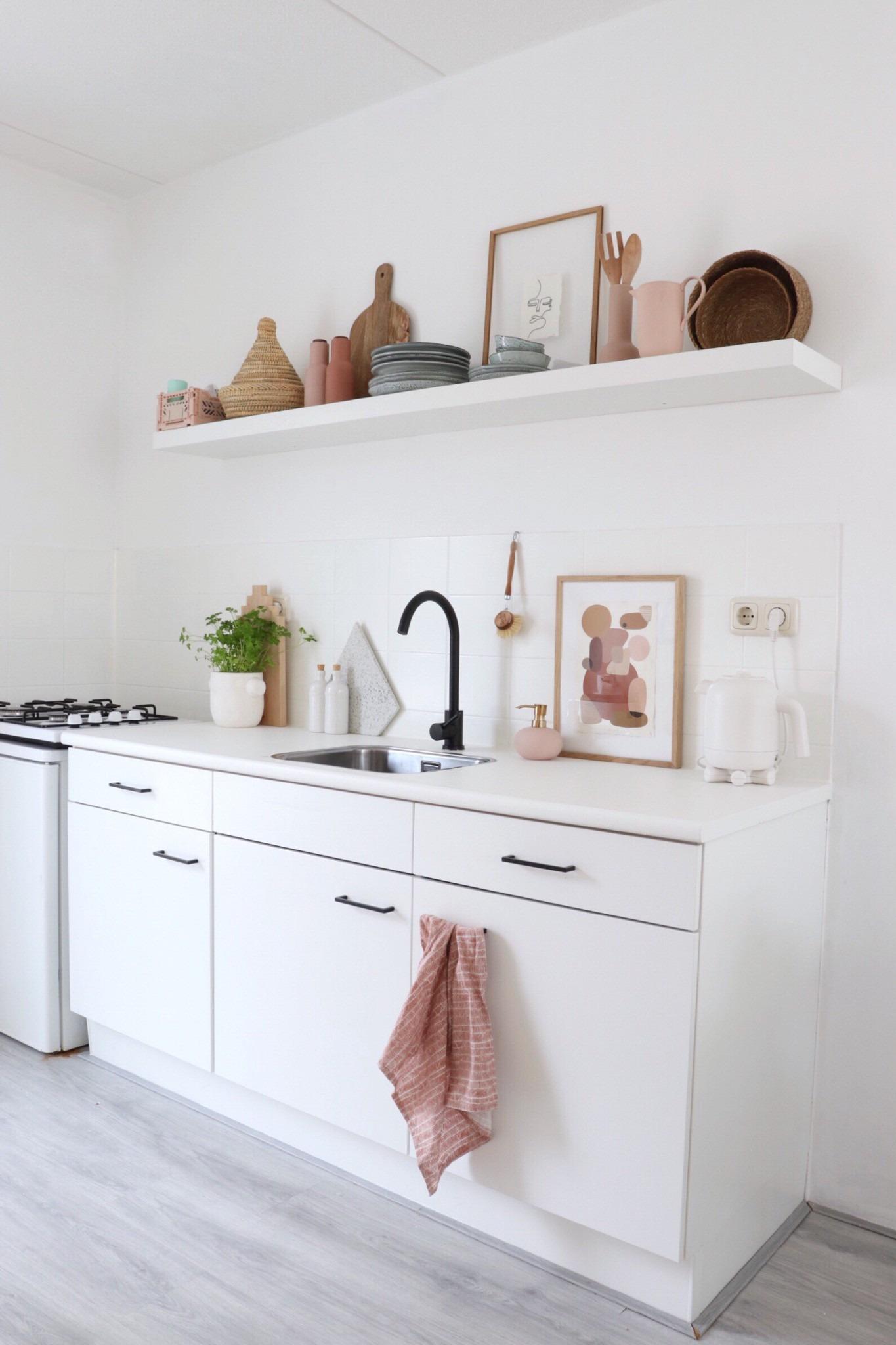 Witte keuken met zwarte en roze kleur accenten.